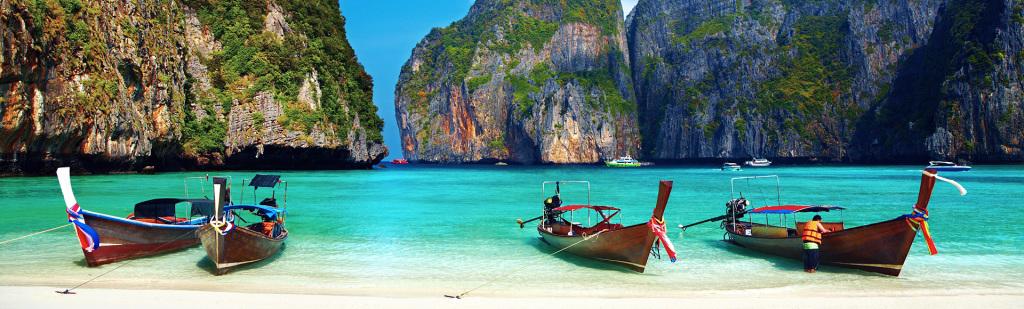 Strand med båtar i Thailand